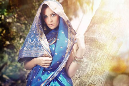 Beautiful lady outdoors in the stylish sari posing in the wild jungle under the summer sunshine Standard-Bild