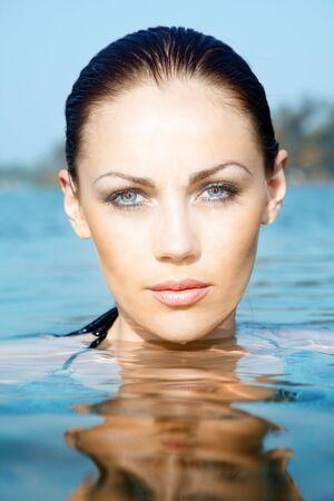 Primo piano del volto della donna graziosa in acqua presso la spiaggia di estate. Foto verticale con luce e colori naturali Archivio Fotografico