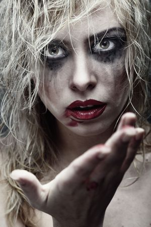 Voodoo female witch with dirty makeup and blood on the hand. Artistic colors and darkness added