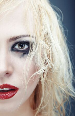 Half face of the blond lady with strange grungy makeup. Vertical photo with natural colors