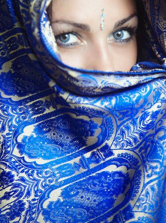 Woman in religious traditional blue cape looking forward. Natural blue colors o eyes Standard-Bild