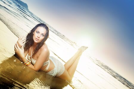 Beautiful lady laying at the ocean beach during summer sunset. Natural colors and lighting Standard-Bild
