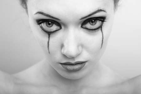 Close-up portrait of the crying woman with washed out mascara. Monochrome photo
