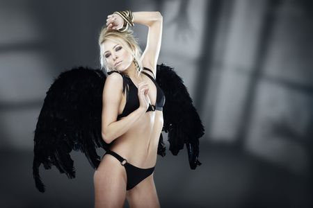 Sexy lady in the lingerie with black angelic wings indoors with horror shadows. Natural colors and darkness
