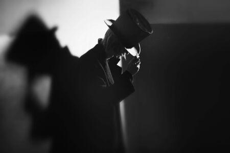Shadowgraph des Mannes in schwarzer Mantel und Hut Standing in der Nähe der Wand und seinen Schatten. Monochrome Foto mit natürliche Dunkelheit. Künstlerische Korn für Film-Effekt hinzugefügt Standard-Bild - 7848811