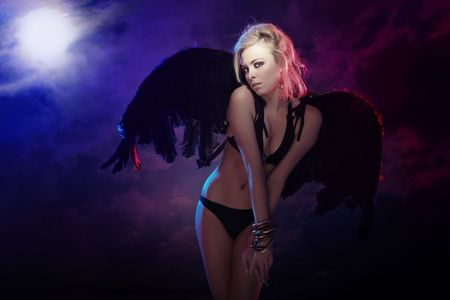 Beautiful blond lady outdoors with black wings. Full moon sky on a background. Artistic colors and darkness added Standard-Bild