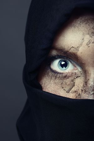 Half face of the human in black hood with damaged skin. Artistic colors and painting added