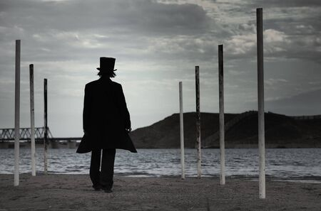 Rear view on alone man in the black coat and top-hat going to the sea. Natural darkness. Artistic colors added Standard-Bild