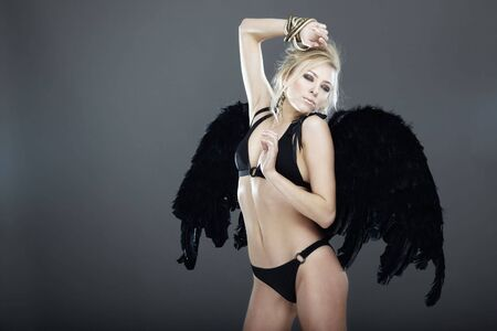 Blond female angel with black angel wings on a dark gray background Stock Photo - 8016266