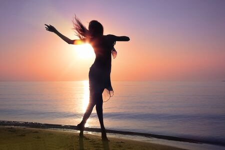Silhouette of the woman dancing at the beach during beautiful sunrise. Natural light and darkness. Artistic vivid colors added Standard-Bild