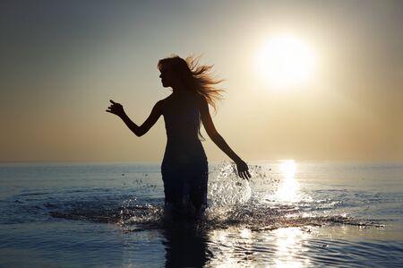 Silhouette der Frau mit langen Haaren zu Fuß in das Wasser während der Sunrise. Natürliche Dunkelheit und Farben Standard-Bild - 8908445