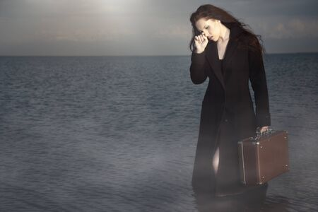 Crying woman in the wet coat holding her luggage and standing in the water. Natural fog and colors