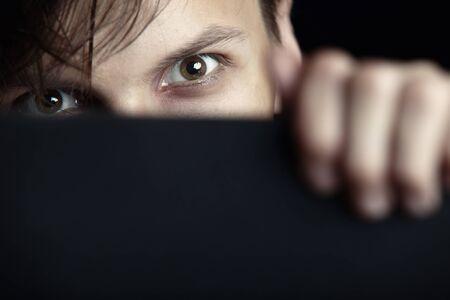 Böse Mann versteckt sich hinter der schwarzen Brett und beobachtet Standard-Bild - 10024033