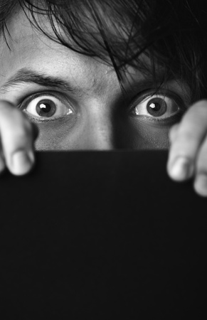 Afraid human hiding behind the dark board. Monochrome photo. Film noir effect added