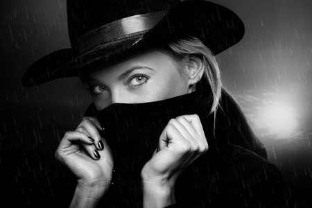 Penal mujer con sombrero de vaquero en el crepúsculo bajo la lluvia. La luz natural y las sombras
