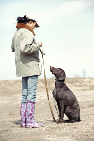 Woman and dog training outdoors