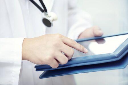Hands of doctor indoors using tablet computer Standard-Bild