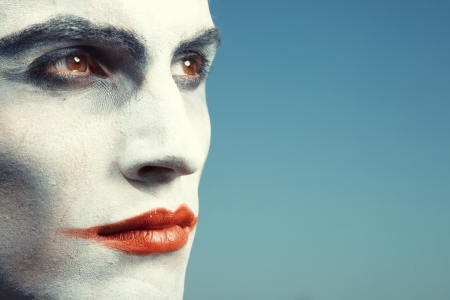 Sad clown with makeup on a blue background