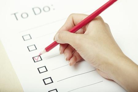 Menschliche Hand schriftlich auf einer Checkliste Dokument Standard-Bild - 15315728