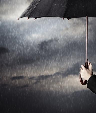 Human hands holding big black umbrella under the heavy rain