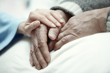 Hand of woman touching senior man in clinic Standard-Bild