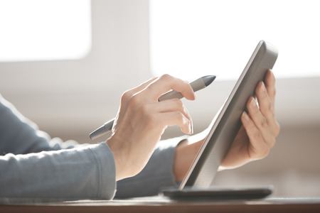 Hands of designer working with tablet PC and stylus