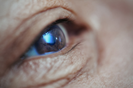 Close-up view on the eye of senior man. Horizontal photo