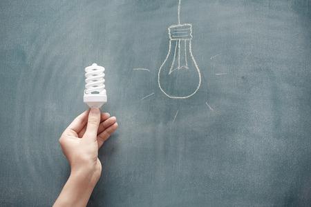 Menschliche Hand, die Energiesparlampe an der Tafel Standard-Bild - 44494507