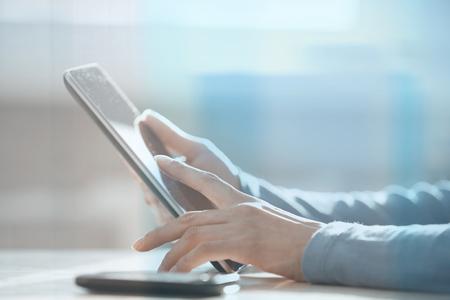 Handen van de vrouw het werken met digitale tablet achter het glas op het kantoor van