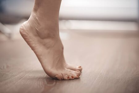 Feet of woman standing on tiptoe at home