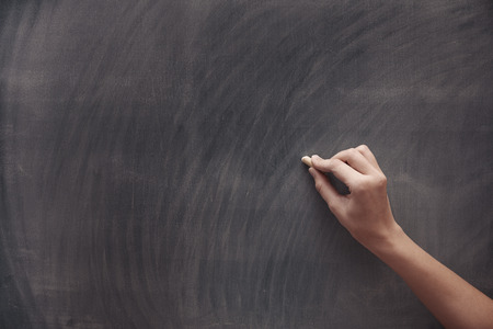 Human hand with chalk at the blackboard