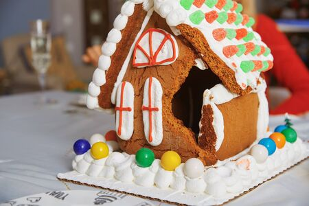 Broken Gingerbread house on the table in Christmas decorated room Foto de archivo - 137670094