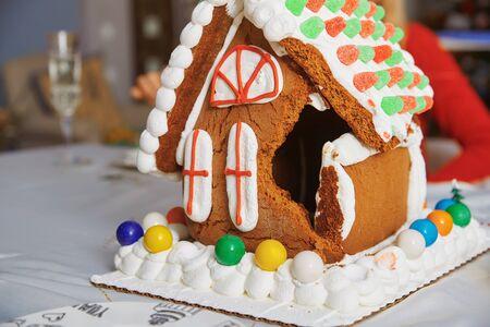 Kaputtes Lebkuchenhaus auf dem Tisch im weihnachtlich dekorierten Raum