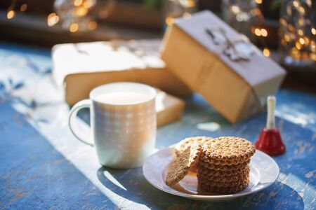 Teacup and Christmas gluten free cookies on a table near the decorated window with gift boxes Standard-Bild