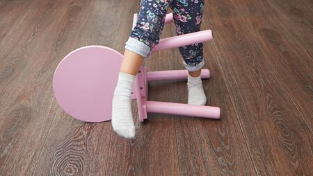 Legs of the child overstepping chair for balance skill development
