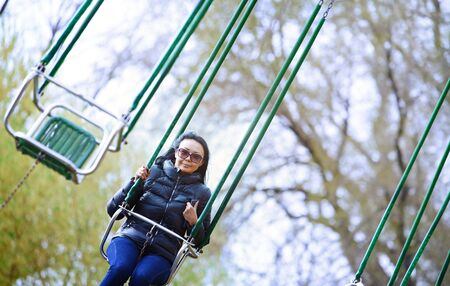 Woman riding on the chain swing at amuzement park