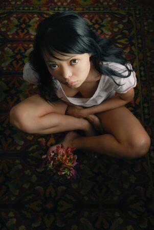 Sensual photo of the lady sitting on the carpet Standard-Bild