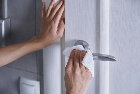 Woman cleaning the door handle with disinfecting wipe Standard-Bild