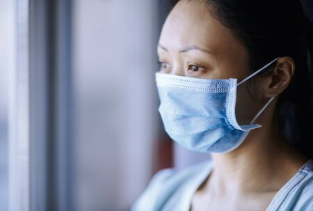Woman staying at home wearing protective surgical mask Standard-Bild