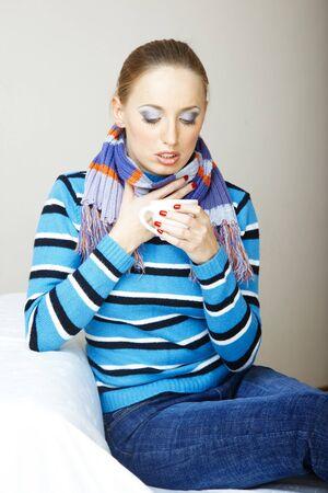 Sick woman drinking hot tea. Indoors photo Standard-Bild
