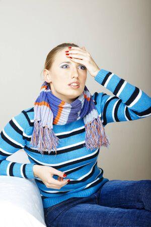 Sad and sick woman sitting indoors. Natural colors
