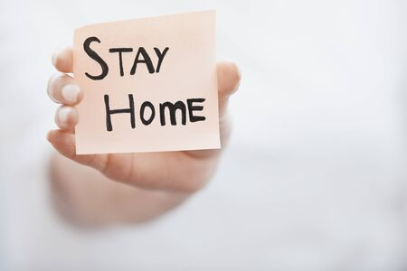 Hand holding sticky note with Stay Home text Standard-Bild