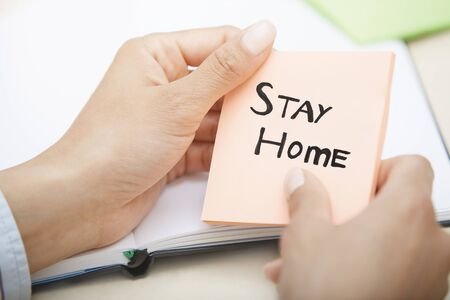 Hands holding pink sticky note with Stay Home text