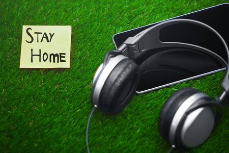 Stay Home text on sticky note on a grass with headphones and digital tablet