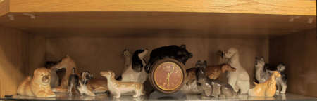 Figurines of dogs near hours on a shelf