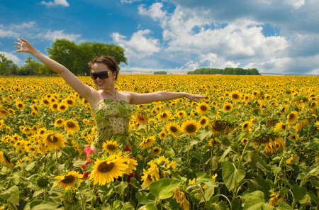 Photo of the girl running in the field of sunflower