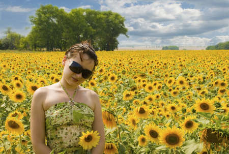Photo of the girl running in the field of sunflowers Stock Photo