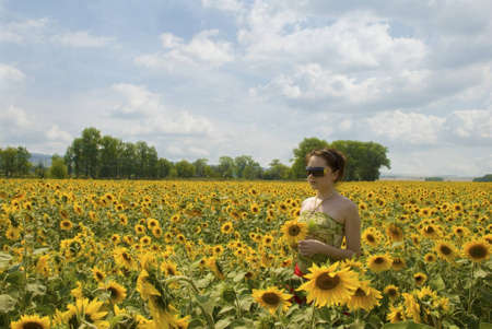 Photo of the girl running in the field of sunflower photo