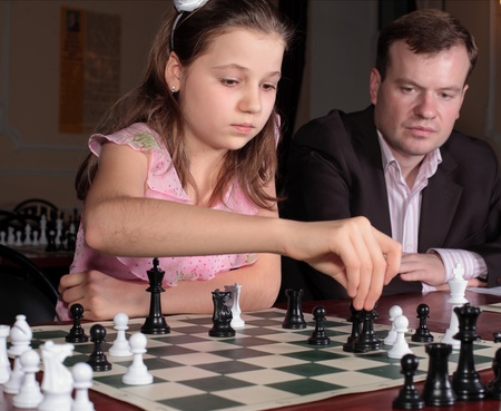 Teenage girl 12-13 years old playing on chess training with chess trainer watching her photo