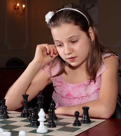 Teenage girl 12-13 years old playing chess Stock Photo - 8266281